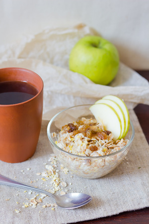 Tasty oatmeal with apple and cup of tea on table photo