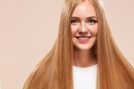 Belle femme blonde modèle de beauté fille avec un maquillage parfait et de longs cheveux raides sur fond clair Banque d'images