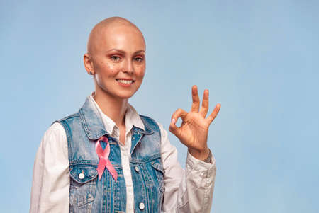 Healthcare and medicine concept. Bald woman with pink cancer awareness ribbon. Happy girl points on copy space