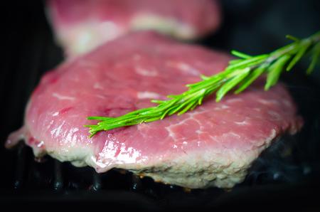 Geschmackvolles Steak auf Grillpfanne während des Kochvorgangs; Close-up-Ansicht mit Fokus auf Rosmarin-Zweig Lizenzfreie Bilder
