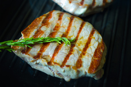 Gegrilltes BBQ Steak auf einer Pfanne braten; Close-up-Ansicht mit Fokus auf Rosmarin-Zweig