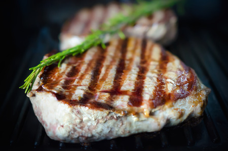 Juicy beef steak cooking on a grill pan with rosemary sprig; Selective focus
