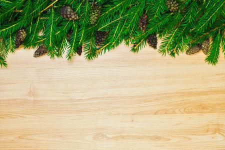 Karácsonyi dekoráció fenyőből és tűlevelű kúpból fából készült háttéren Stock fotó