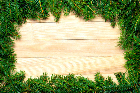 Christmas fir branches frame on wooden board. Christmas background or greeting card Stockfoto