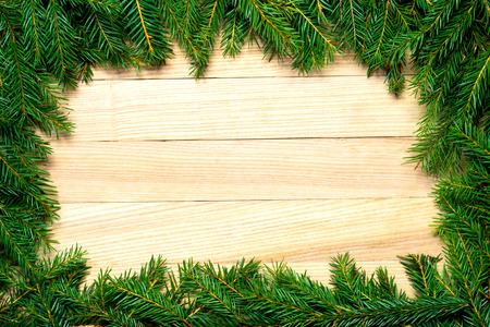 Karácsonyi fenyő ágak keret a fa táblán. Karácsonyi háttér vagy üdvözlőlap
