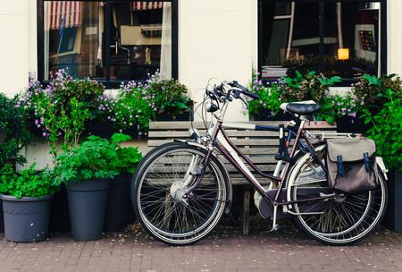 Twee fietsen die op een pittoreske straat in Amsterdam verblijven Stockfoto