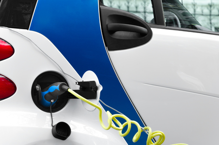 Electric car chargering on the station. Power supply plugged into an electric car being charged. Alternative  ecological fuel. Stockfoto