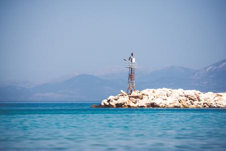 美麗的海景與岩石岸上的燈塔 版權商用圖片