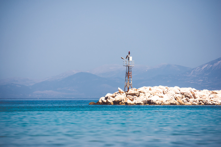 Mooi zeegezicht met baken op rotsachtige kust Stockfoto