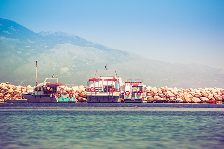 Csónakok felkeltek a sziklás mólón napfelkeltével Stock fotó