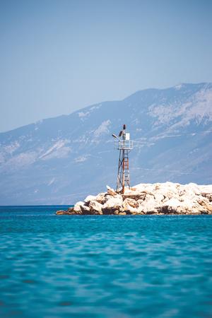 孤獨的海上信標在岩石的岸邊。垂直方向 版權商用圖片