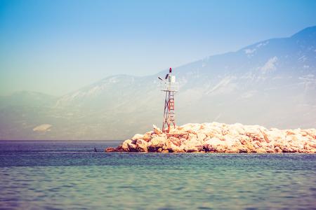 Roca de mar rocoso con faro en la salida del sol Foto de archivo