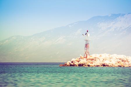 Roca de mar rocoso con faro. Foto de orientación horizontal.