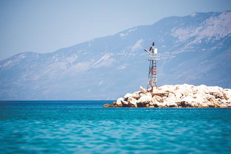 Rocky orilla del mar con faro en el día de verano