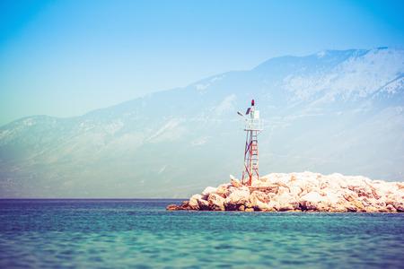 Tengeri beacon a sziklás parton napfelkelte alatt