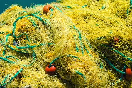 Red de pesca amarilla con flotadores y cuerdas. Concepto náutico. Foto de archivo