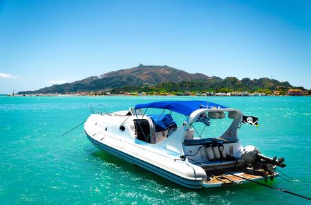 Barco en las aguas azules del mar con la isla verde en fondo. Paseo marítimo en el barco. Verano viajando. Foto de archivo