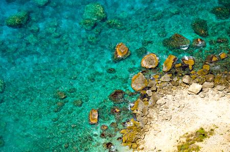 Luchtfoto foto. Mooi rotsstrand met doorzichtig azuurblauw water, scherpe kliffen en kiezelstenen. Verbazingwekkende kust met turkoois water. Uitnemen van drone Stockfoto
