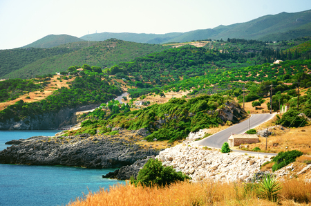 山景觀與橄欖園,天藍色海岸和驚人的蜿蜒的岩石道路的全景。夏天的背景 版權商用圖片