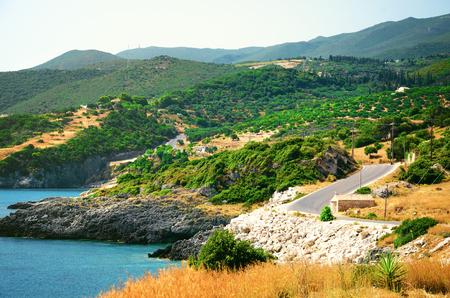Panoramablick auf Berglandschaft mit Olivenhainen, azurblaue Meeresküste und erstaunliche kurvenreiche Felsenstraße. Sommertag Hintergrund