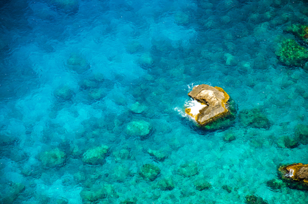 Sea aerial top view. Rocky beach with azure water and reefs. Transparent water with sea bottom and underwater life. Banco de Imagens