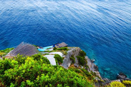 Trappen naar de zee rotsachtige kust, met ligstoelen. Bovenaanzicht naar de rotsachtige baai.