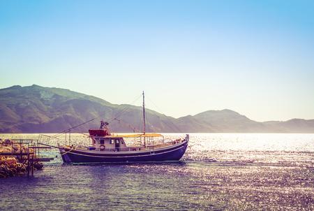 Vitorlázó hajó kikötve a mólón napkelte után.
