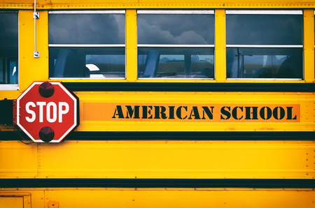 Classic yellow american school bus transporting children to the school. Back to school concept. Red stop sign on school bus side.