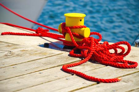 Bordetje vastgemaakt aan de bollard bij de pier. Nautische touwtouw.