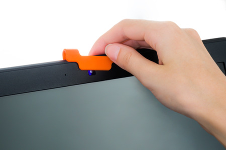 Human hand covering a webcam of laptop with rubber cover to prevent spying. Digital security concept