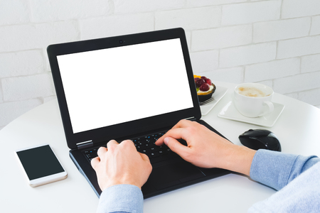Mockup photo of laptop with blank white screen. Man working on laptop at the table from cafe. Banco de Imagens