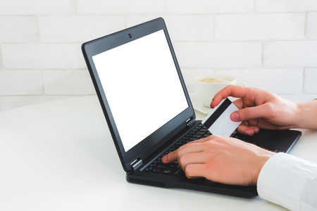 Mockup photo with laptop and man hands holding credit card entering verification code. Online payment concept