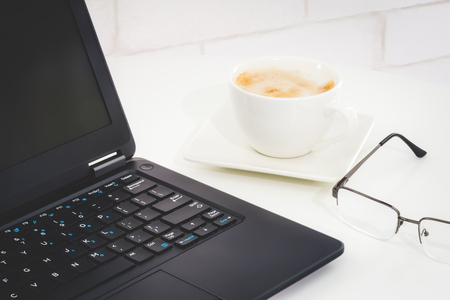 Office desktop with laptop, eye glasses and a cup of coffee