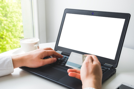 Online payment mockup. Mans hand holding credit card and entering private data to the laptop to make transaction.