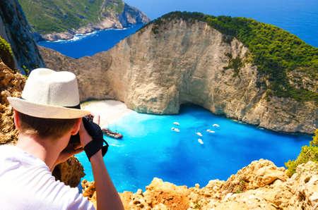 Tourist taking photo of famous resort in Greece, Navagio beach. Summer vacation on Zakynthos island. Stock Photo