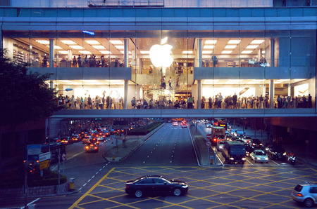 the central bank: People make a purchases in the Apple store near street with cars move alongside the Central district of Hong Kong