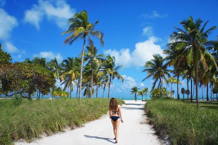 stated: Miami Beach, United States - February 4, 2016: Girl walk at the sunny Crandon park Beach of Key Biscayne near Atlantic Ocean.