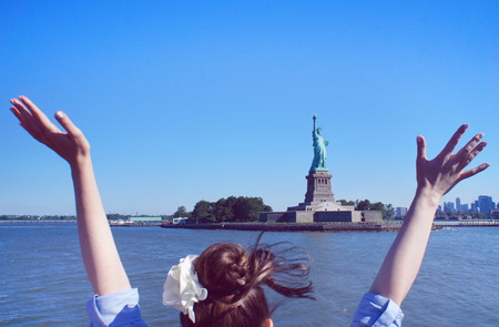 salutes: New York, United States - June 22, 2015: Girl salutes the Statue of Liberty at the Liberty Island in the New York City. Stock Photo