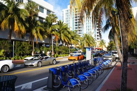 bycicle: Miami, United States - February 5, 2016: People and cars move down the street near bycicle parking in the Miami Beach.