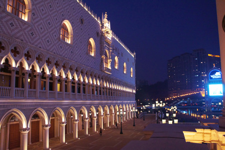 doge's palace: Macau, Macau S.A.R. - November 23, 2015: People walk alongside the Macau Venetian casino Doges Palace copy resort in Macau by night.