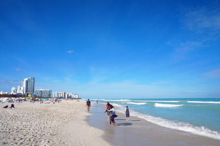 sunny south: Miami Beach, United States - February 8, 2016: People walk and relax at the sunny South Beach of Miami near Atlantic Ocean. Editorial