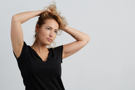 Emotional beautiful young adult woman portrait. Studio shoot. Isolated on White Background. A woman in a black T-shirt with a deep neckline lifted her hair with her hands and looks to the right. Banco de Imagens