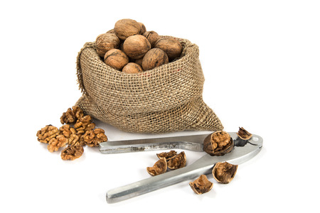 high calorie: Walnuts in a bag and the tool for their splitting on the white isolated background