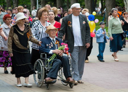 grandad: VOLGOGRAD, RUSSIA - MAY 9, 2010: World War II veteran in a wheelchair and accompanied by relatives on Victory Day celebration on the Avenue of Heroes in Volgograd