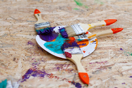 osb: Paints and brushes on OSB board Stock Photo