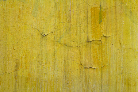 mangy: Old yellow paint with cracks on the wall