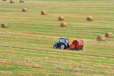 baler: Tractor pulls Round Baler in the background of a field with haystacks