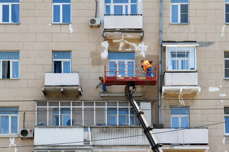 reconstructing: RUSSIA, MOSCOW - JUNE 18, 2015: Two construction workers in bucket of crane vehicle are reconstructing the facade of building in Moscow