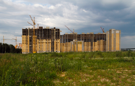Industrial landscape, construction of prefabricated houses with cranes