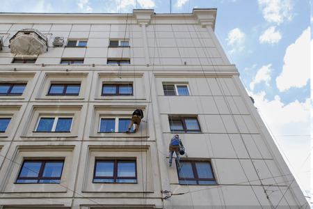 reconstructing: RUSSIA, MOSCOW - JUNE 18, 2015: Team of construction climbing workers reconstructing the facade of building in Moscow Editorial